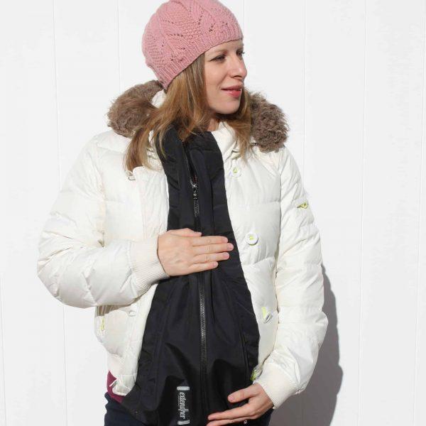 Pregnant woman wearing maternity coat extender